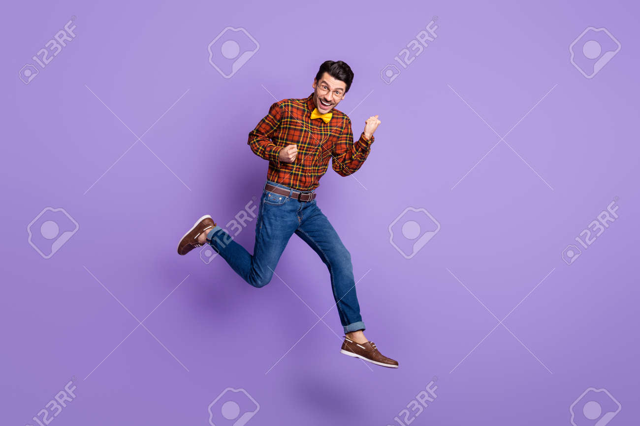 Full size photo of young handsome cheerful smiling positive man jumping in victory isolated on violet color background - 167187438