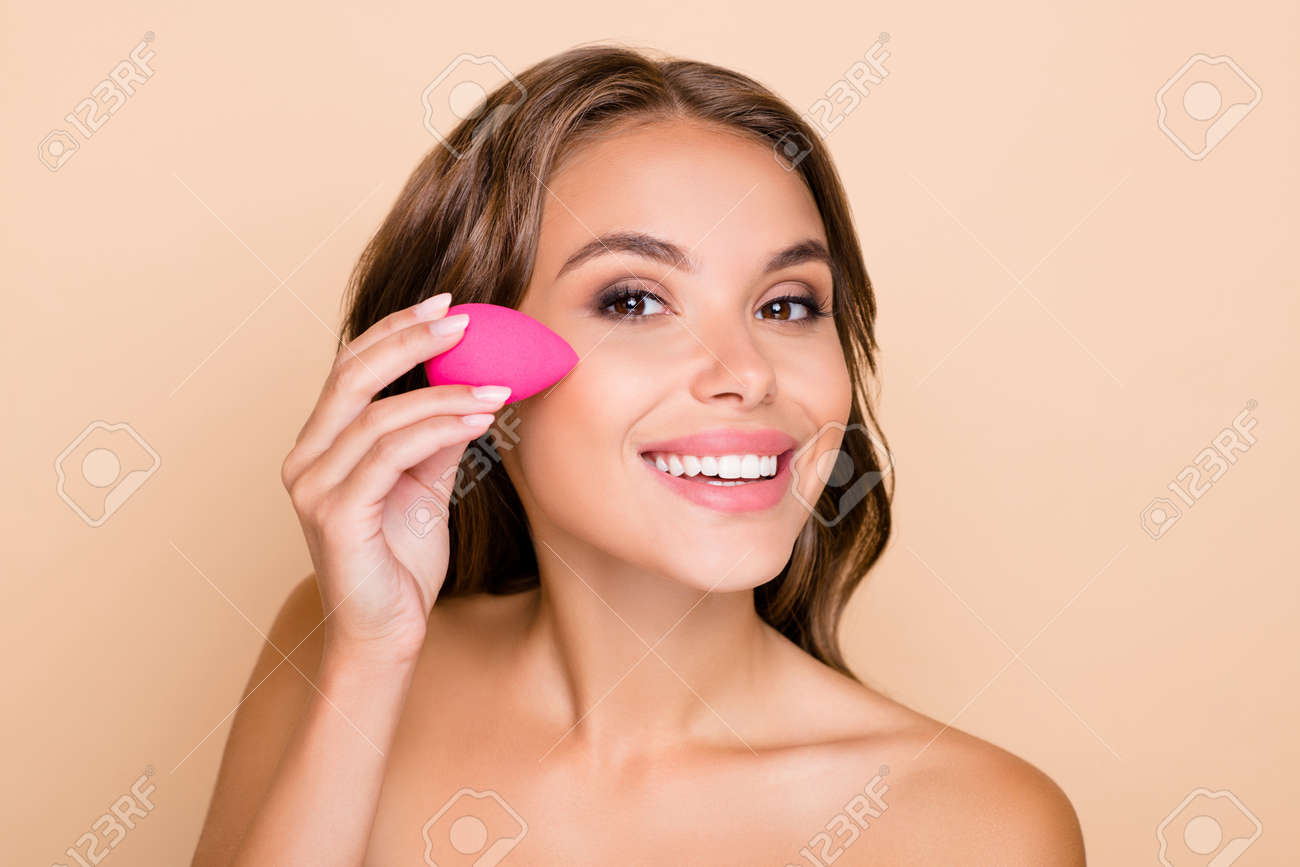 Photo of young beautiful smiling woman applying foundation on cheek with beauty blender isolated on beige color background - 168128258