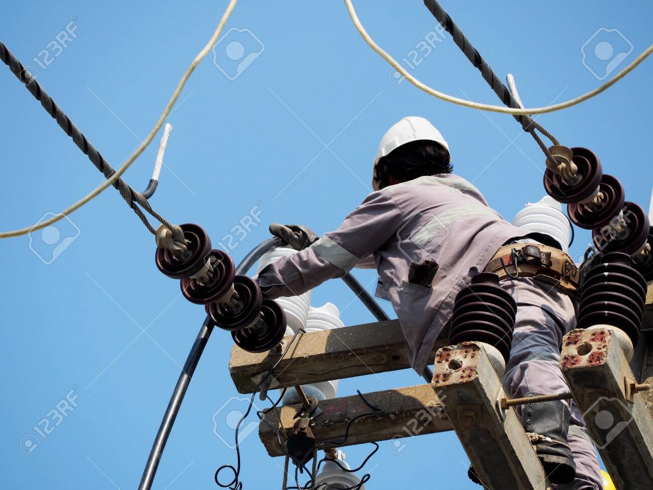 electrician man working at height and dangerous ,high voltage power line maintenance - 145604426
