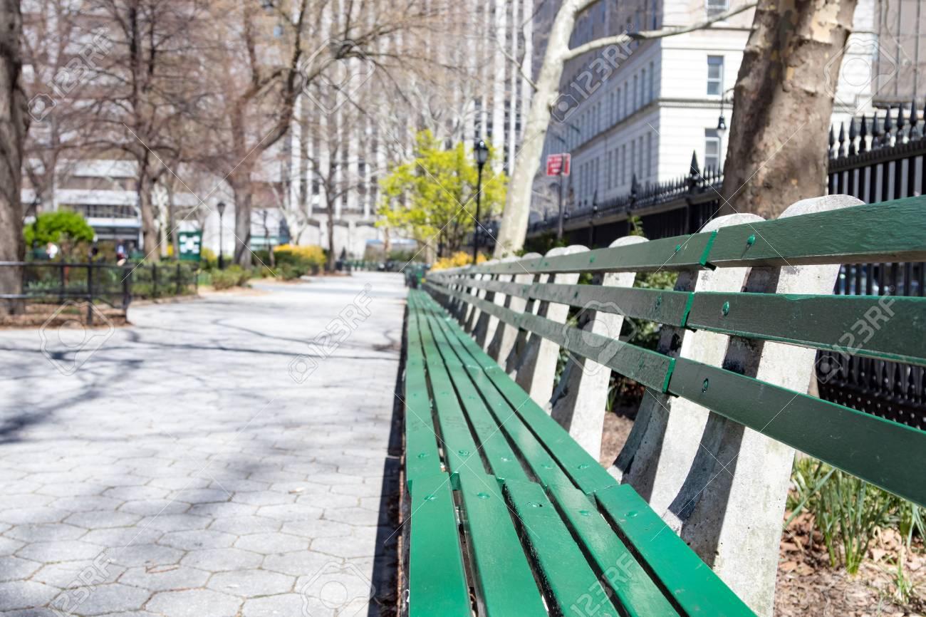 Sunlight Shines On Empty Park Bench In Manhattan New York City