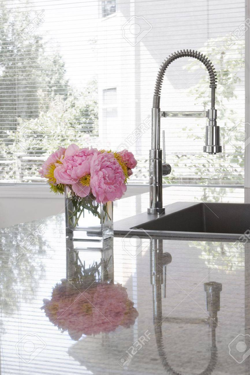 vase of pink peonies and chartreuse chrysanthemums on sink of modern kitchen - reflection in granite countertop Stock Photo - 6186496