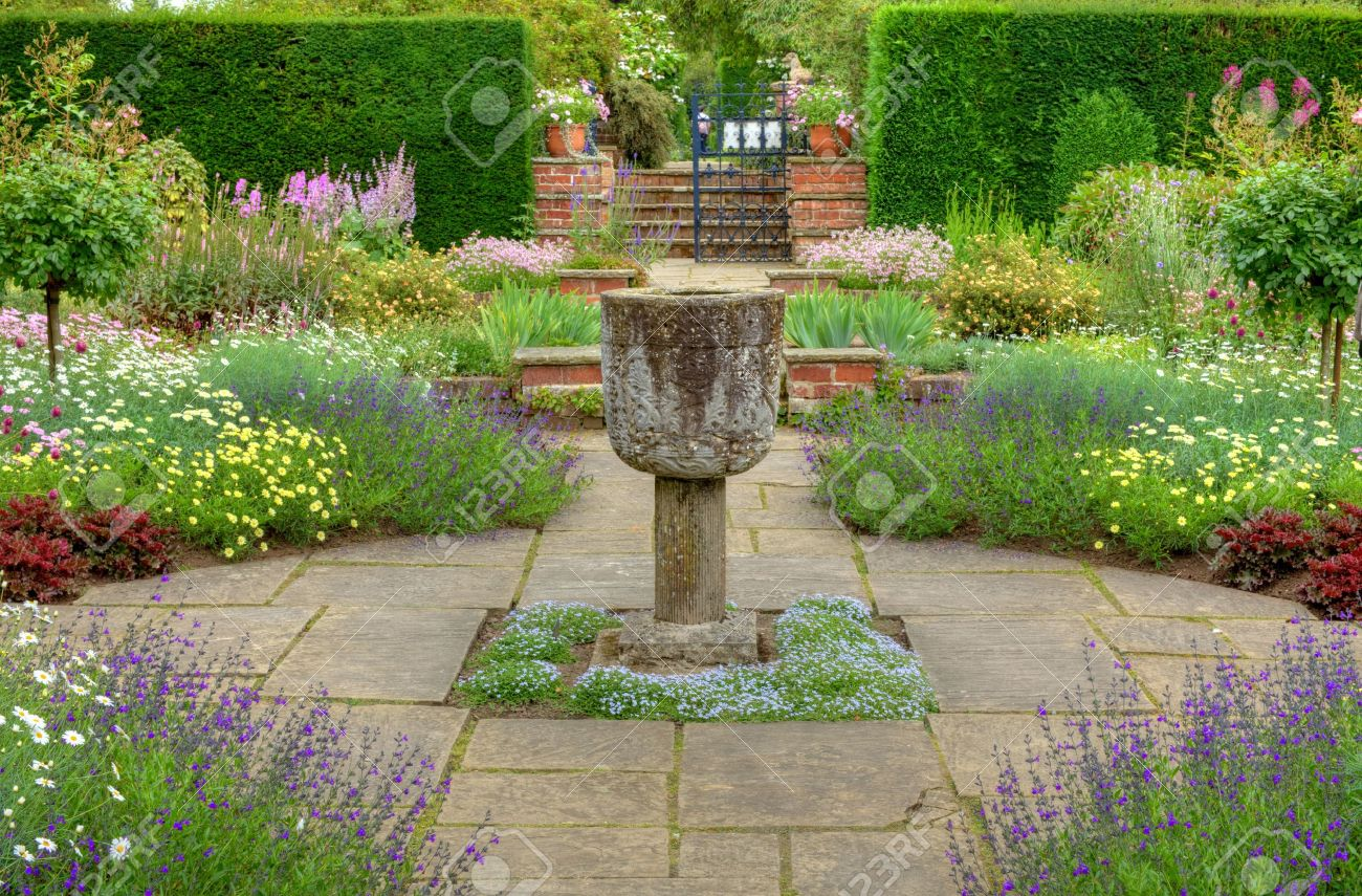 Flagged garden with a stone vase ornament and summer flowers - 16504275