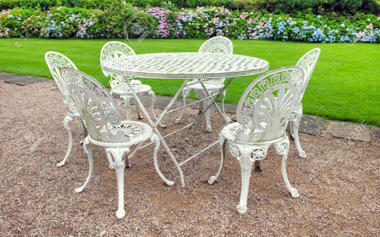 Wrought iron table and six chairs in an English garden