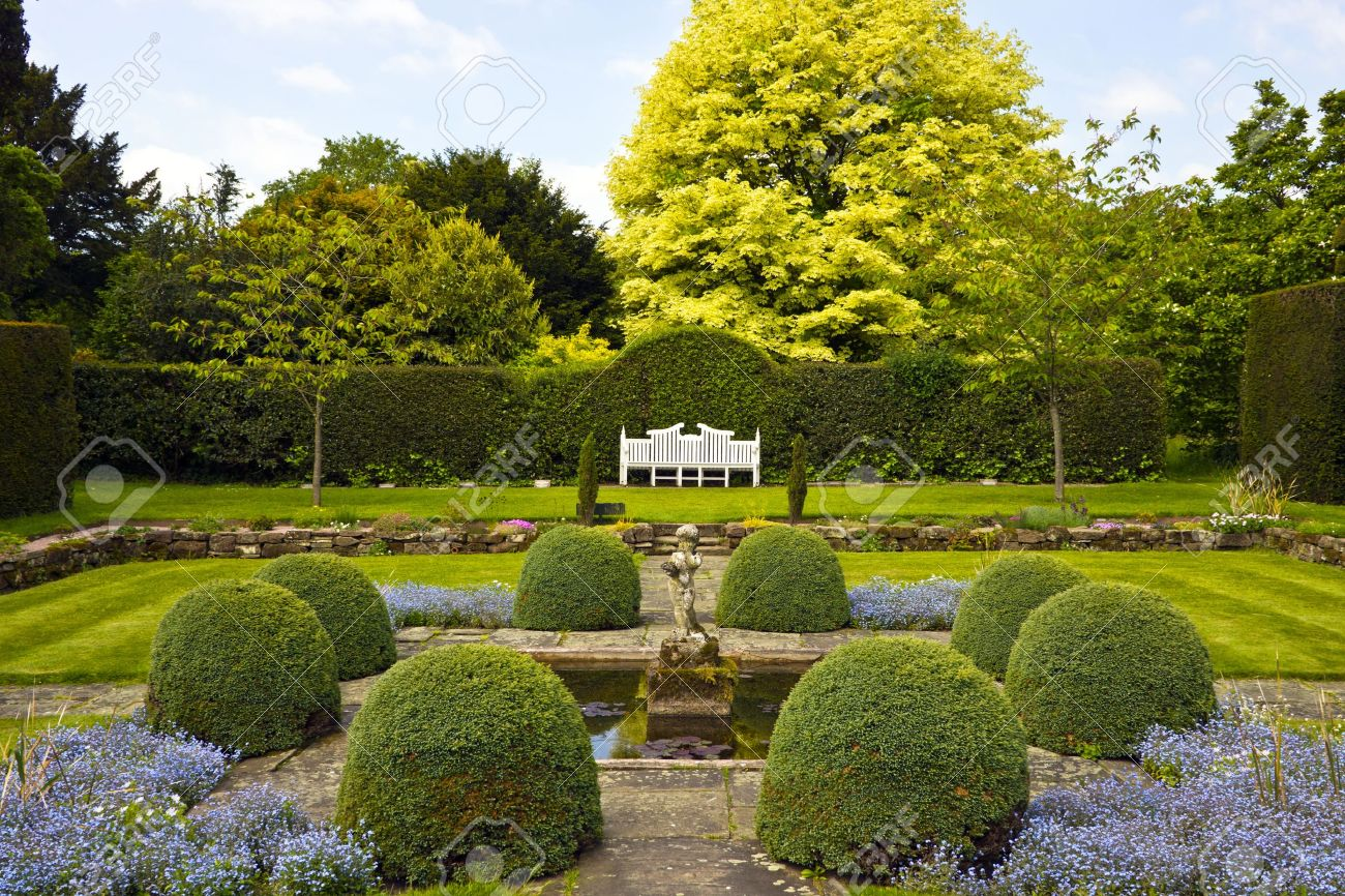 Formal English garden with topiary shrubs and stone ornament by the pond - 20441282