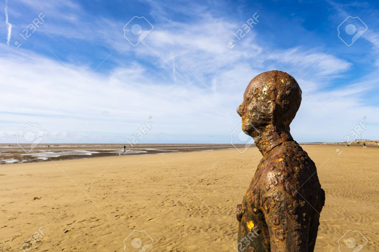 CROSBY BEACH, ENGLAND - SEPTEMBER 13, 2016: Detail of Another Place by Antony Gormley consists of 100 cast-iron, life-size figures spread out along three kilometres of the foreshore near Liverpool. - 63347190