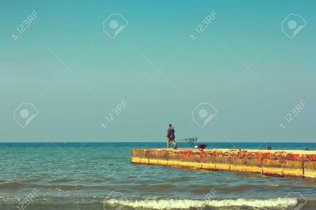 Archivio Fotografico - L uomo è un pescatore con una canna da pesca sul  frangiflutti 0a74744776eb
