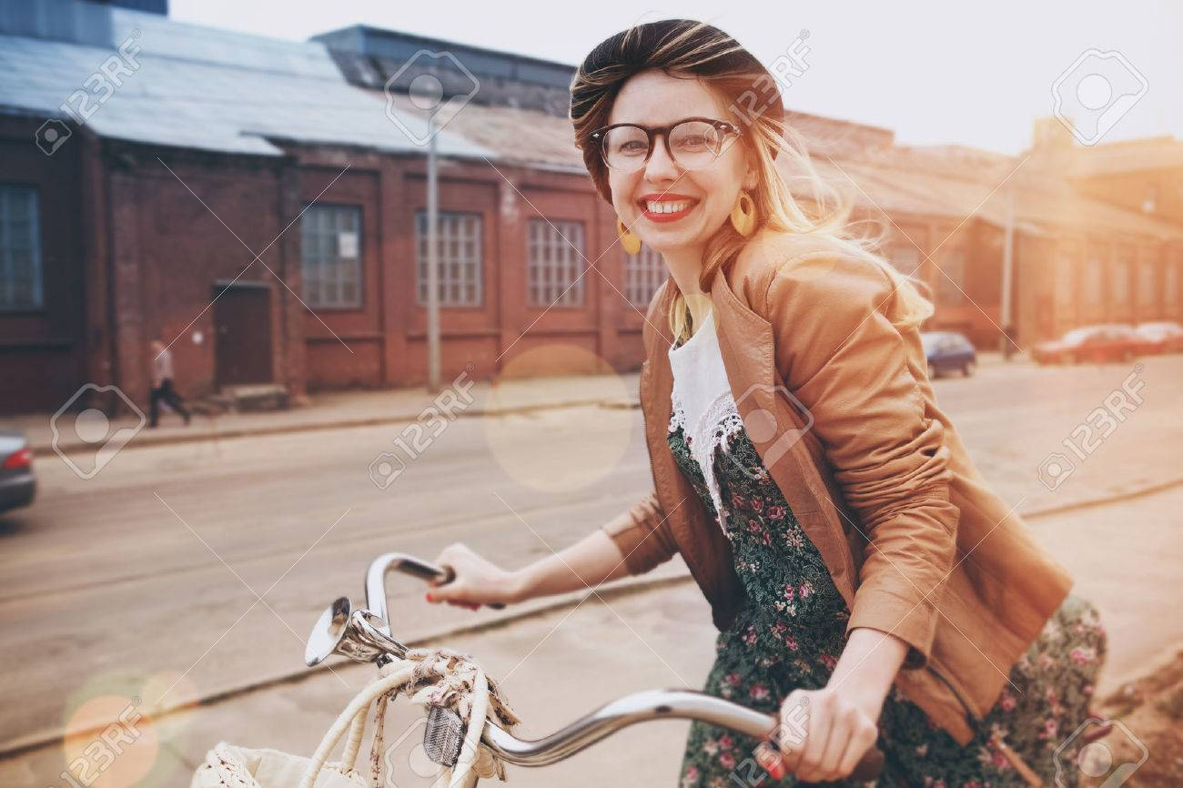 stylish woman riding on bike in morning sunshine Stock Photo - 46657546