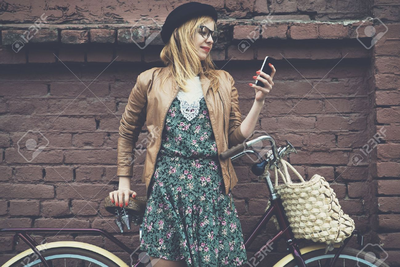 City lifestyle stylish hipster girl with bike using a phone texting on smartphone app in a street Stock Photo - 46656418