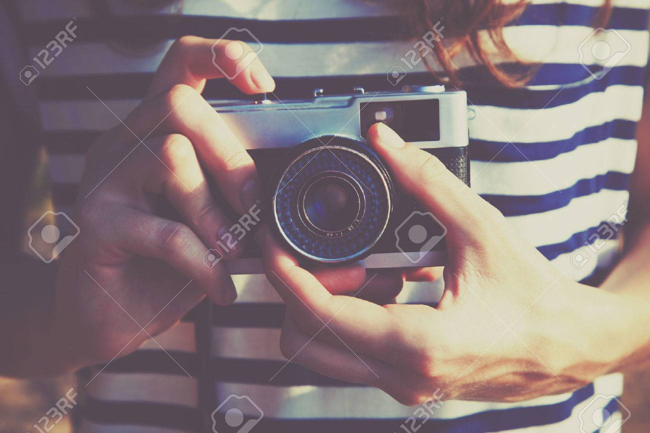 girl holding retro camera and taking photo Stock Photo - 46656344