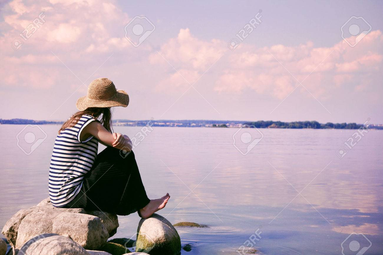 stylish woman alone sitting on stone coast and looking at sea Stock Photo - 46656351