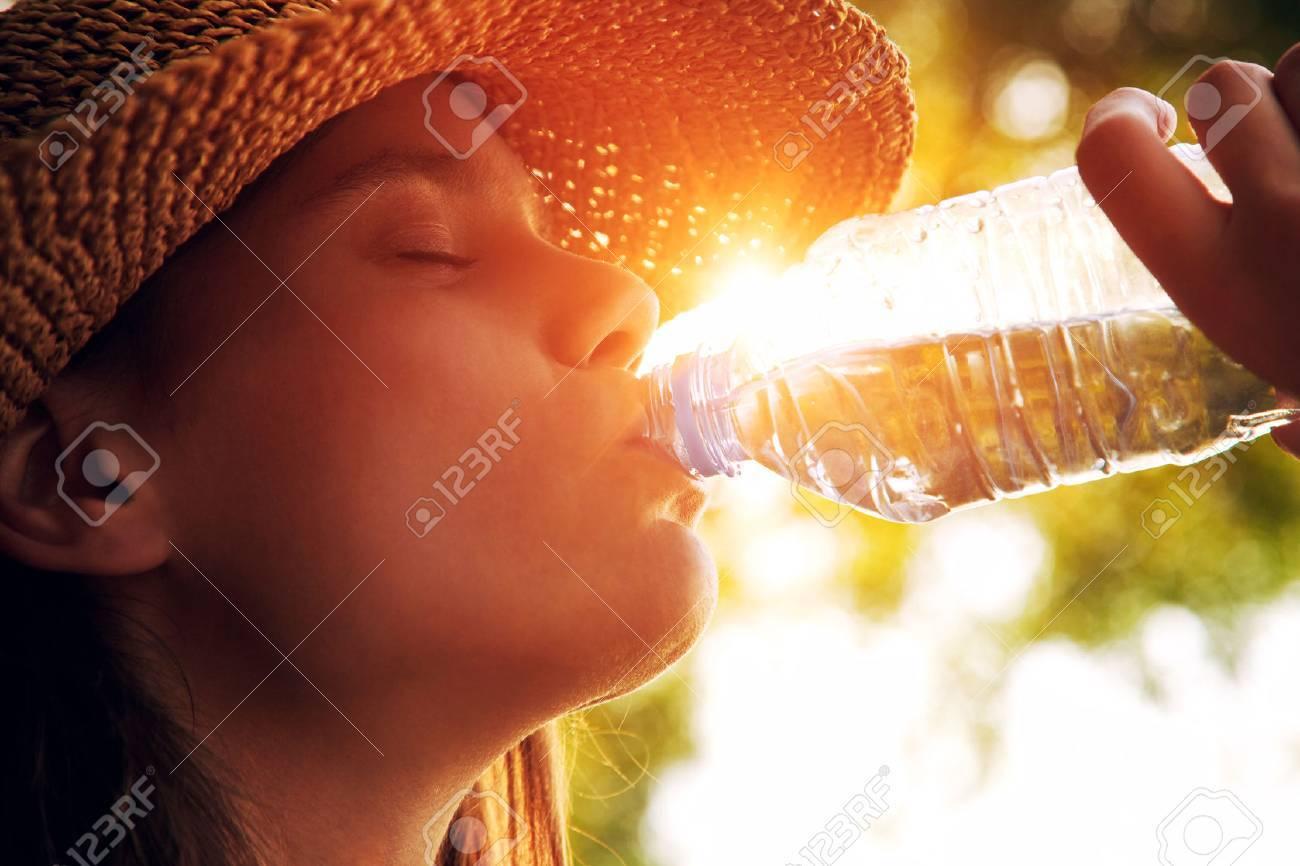 Woman drinking water in summer sunlight Stock Photo - 46656183