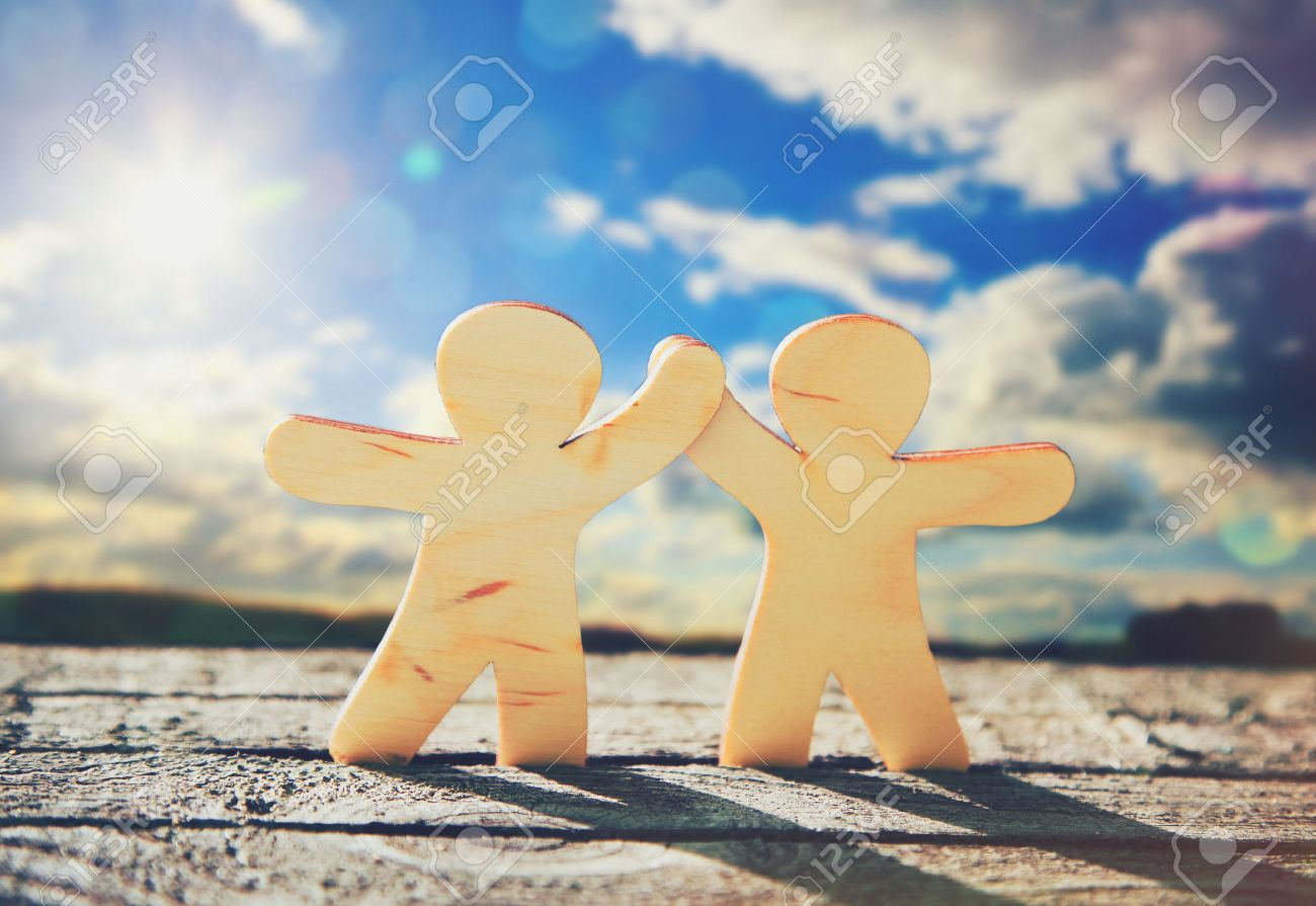 Wooden little men holding hands on sky and sun background. Symbol of friendship, love and teamwork Stock Photo - 46651308