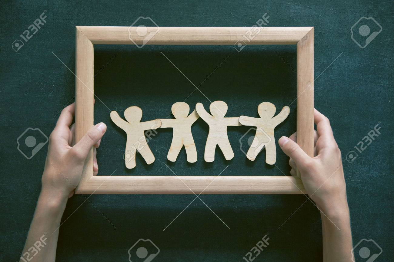 Wooden little men holding hands in frame on blackboard background. Symbol of friendship, safeness or teamwork concept Stock Photo - 46651046