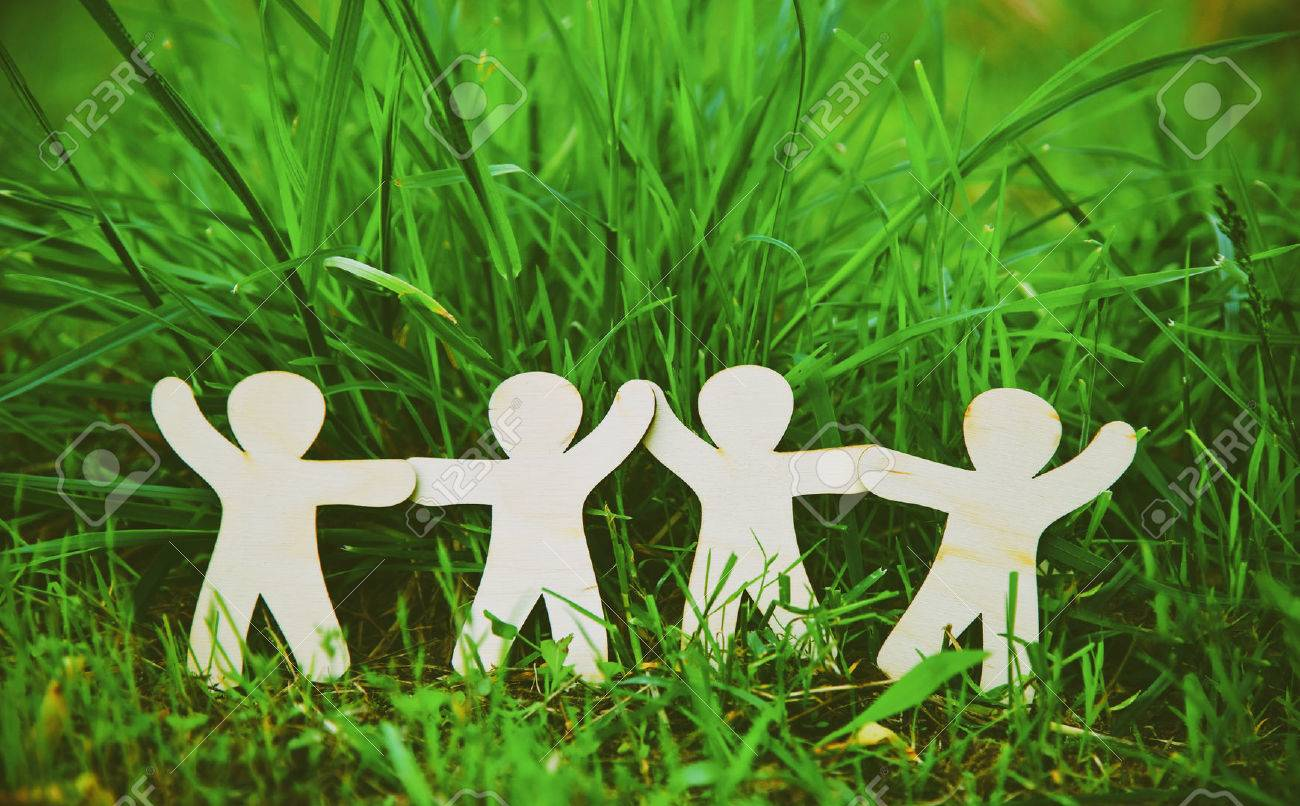 Wooden little men holding hands in summer grass. Symbol of friendship, family, teamwork or ecology concept Stock Photo - 46651047