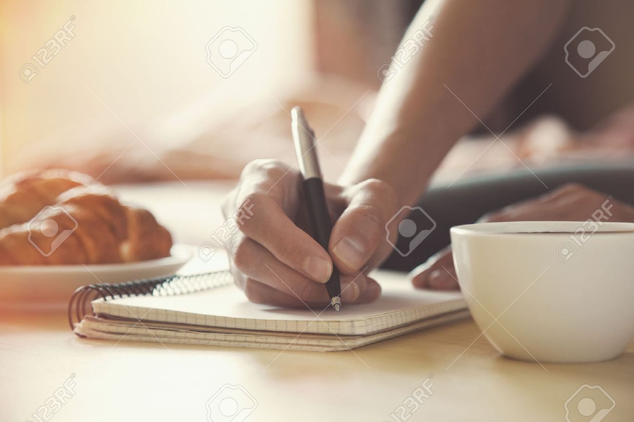 female hands with pen writing on notebook with morning coffee and croissant Stock Photo - 46651062