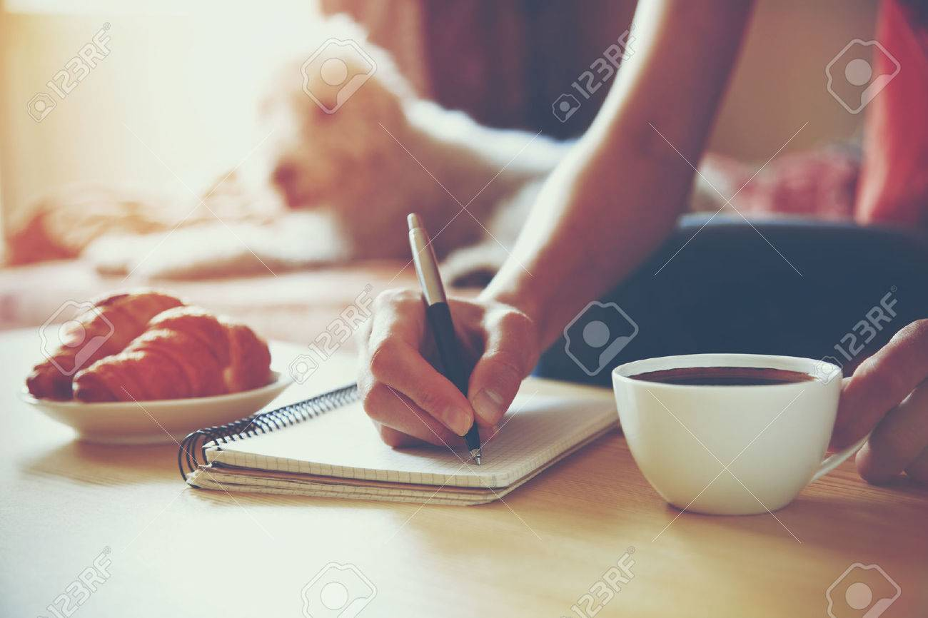female hands with pen writing on notebook with morning coffee and croissant Stock Photo - 46650863