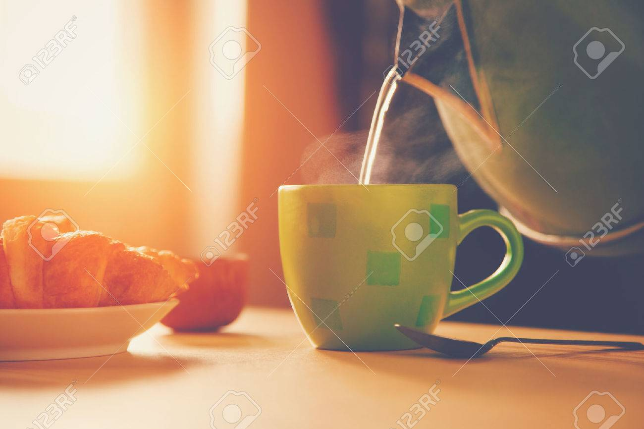 kettle pouring boiling water into a cup during breakfast in morning sunlight Stock Photo - 46650757