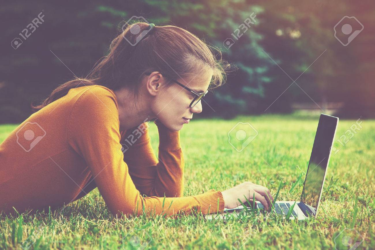 Smiling girl with glasses lying on the grass and using laptop and typing Stock Photo - 46616735