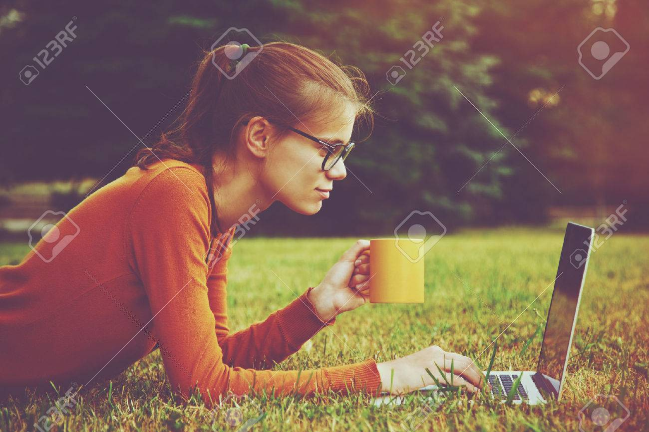 girl lying on the grass and using laptop and typing with coffee or tea mug - 46616741