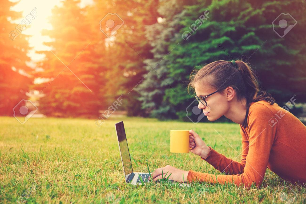 girl lying on the grass and using laptop and typing with coffee or tea mug. copy space Stock Photo - 46616747
