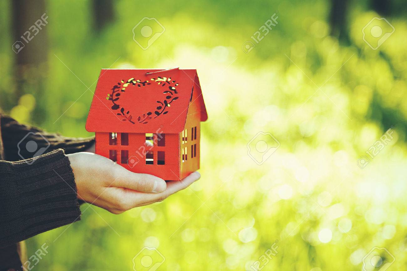 hands holding red model of house as symbol on natural garden background Stock Photo - 46650775
