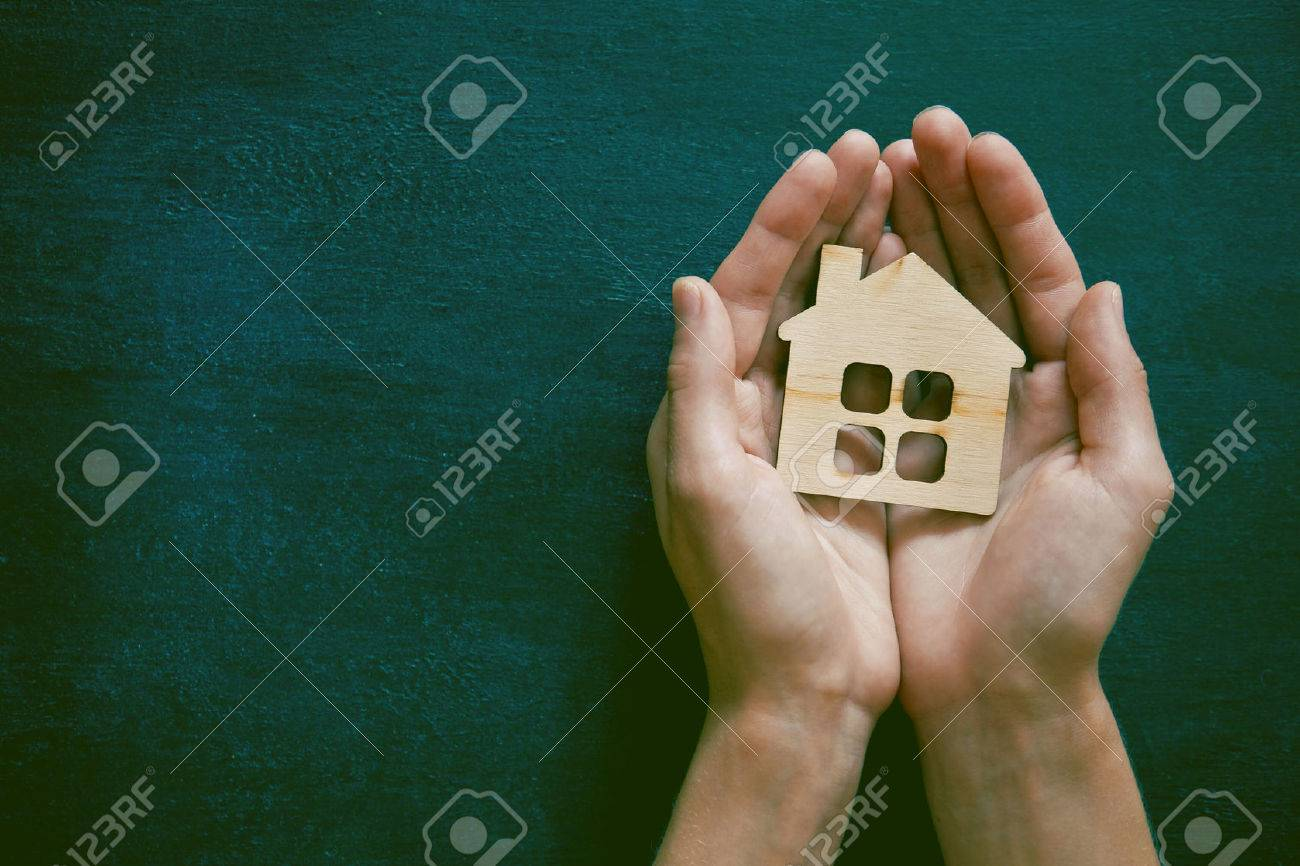 Hands holding little wooden house on blackboard background. Symbol of construction, security or sweet home concept Stock Photo - 46650596