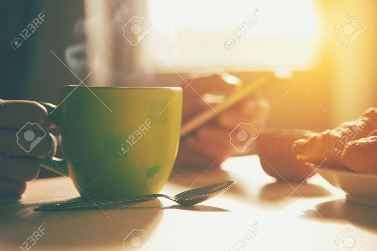 fresh breakfast with hot coffee and browsing smartphone in morning sunlight Stock Photo - 46650602