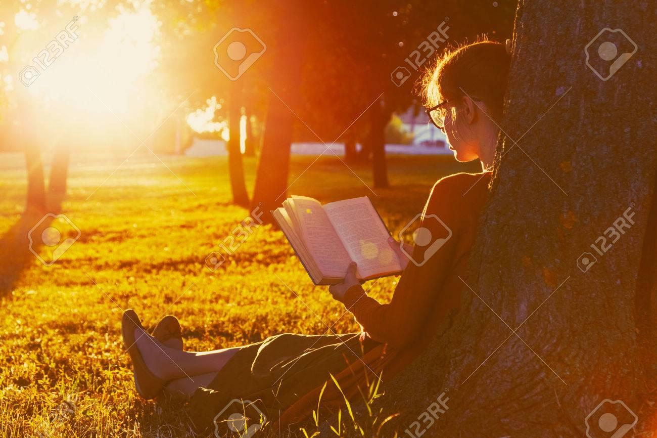 girl reading book at park in summer sunset light Stock Photo - 46616702