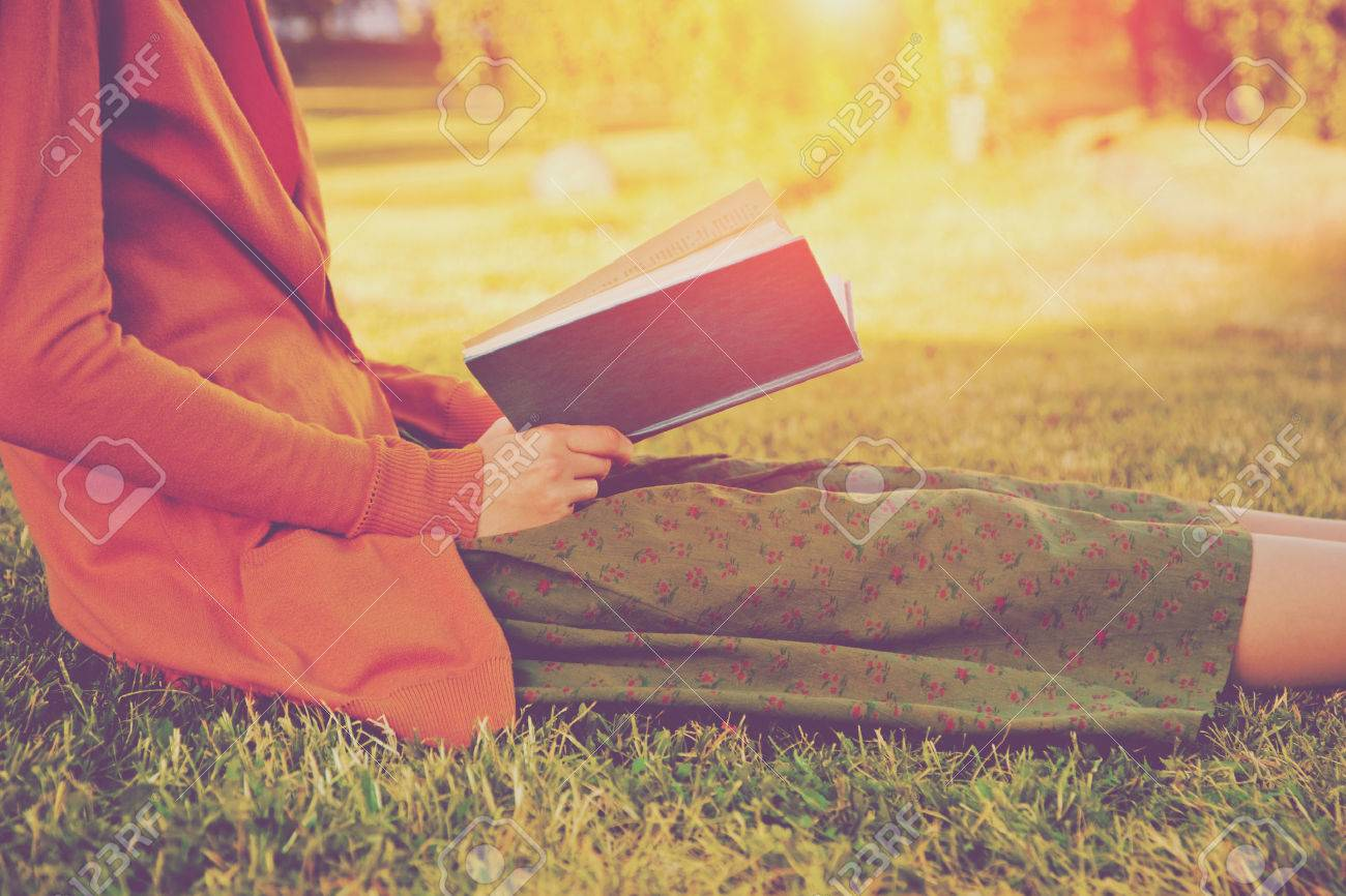 girl reading book at park in summer light Stock Photo - 46650601