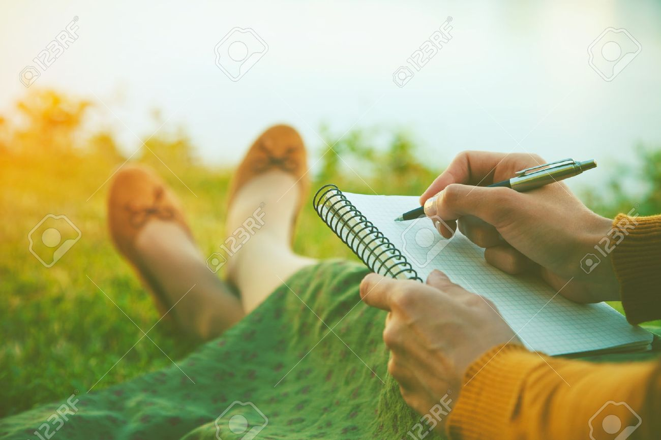 female hands with pen writing on notebook on grass outside Stock Photo - 46650488