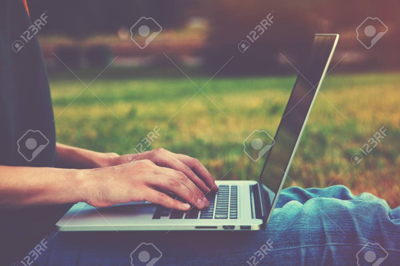 Hands using laptop and typing outside on nature background Stock Photo - 46650115