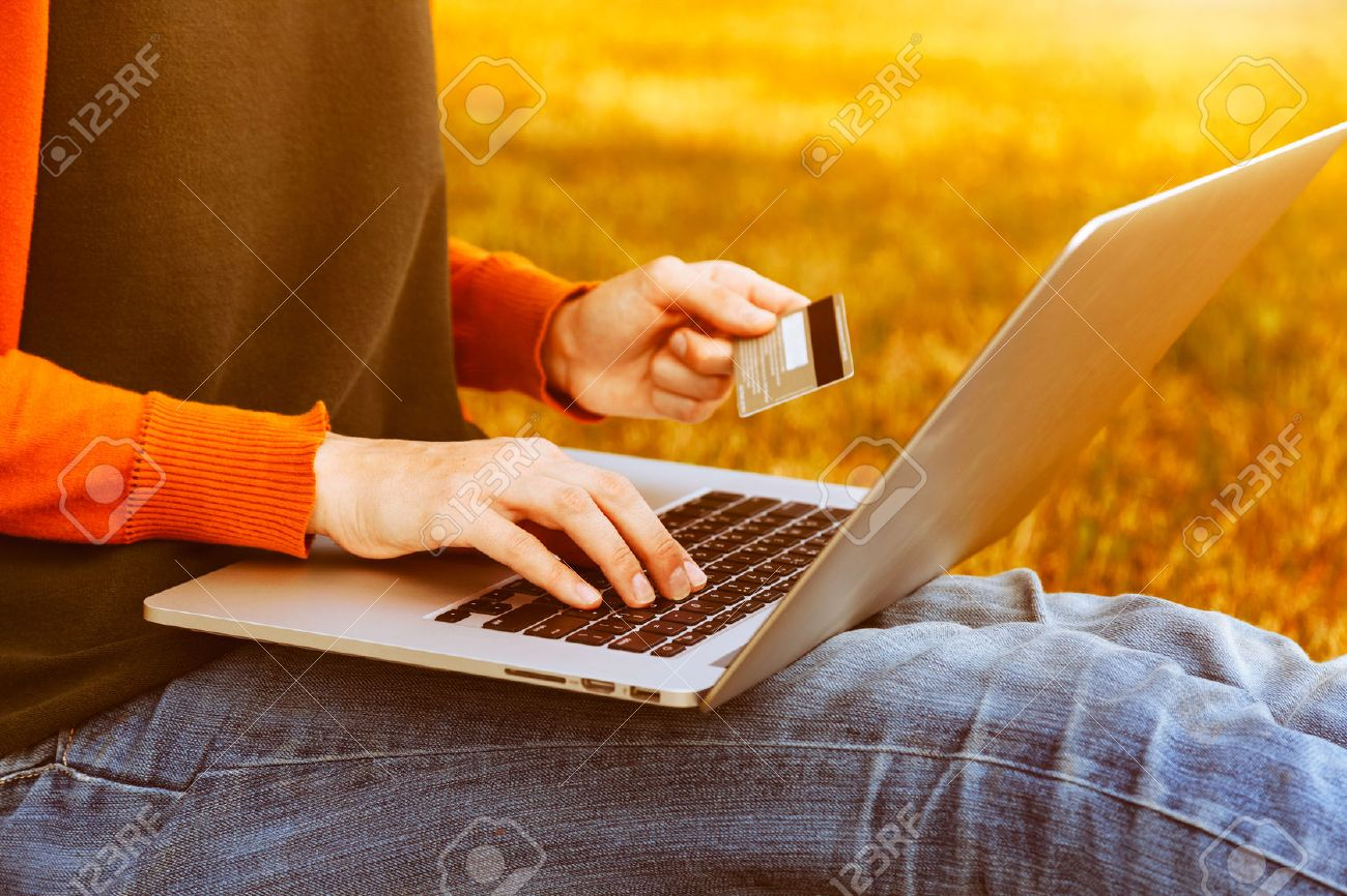 Hands holding credit card and using laptop on natural summer background. Online shopping Stock Photo - 46650119