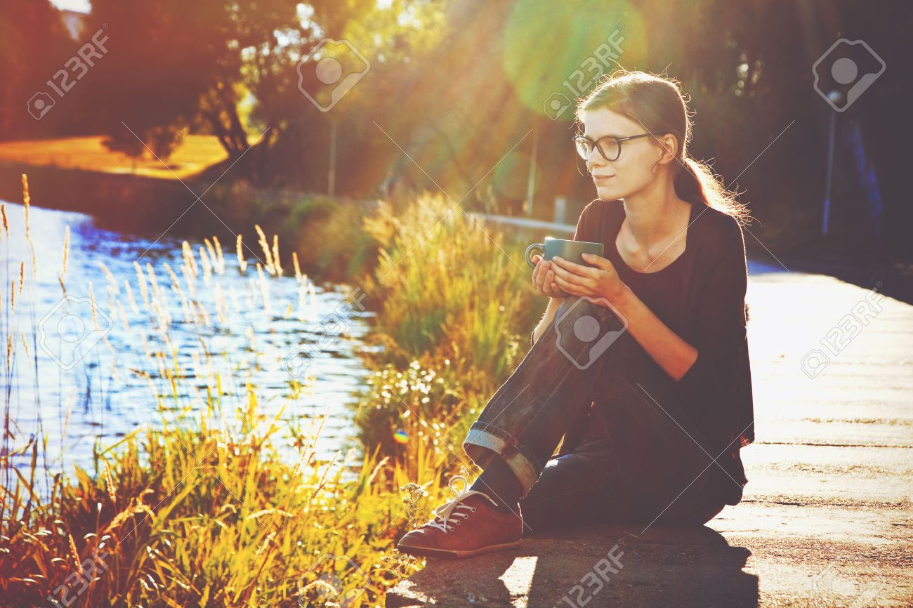 Smiling girl with cup of tea or coffee enjoying on summer shore of river Stock Photo - 46674951