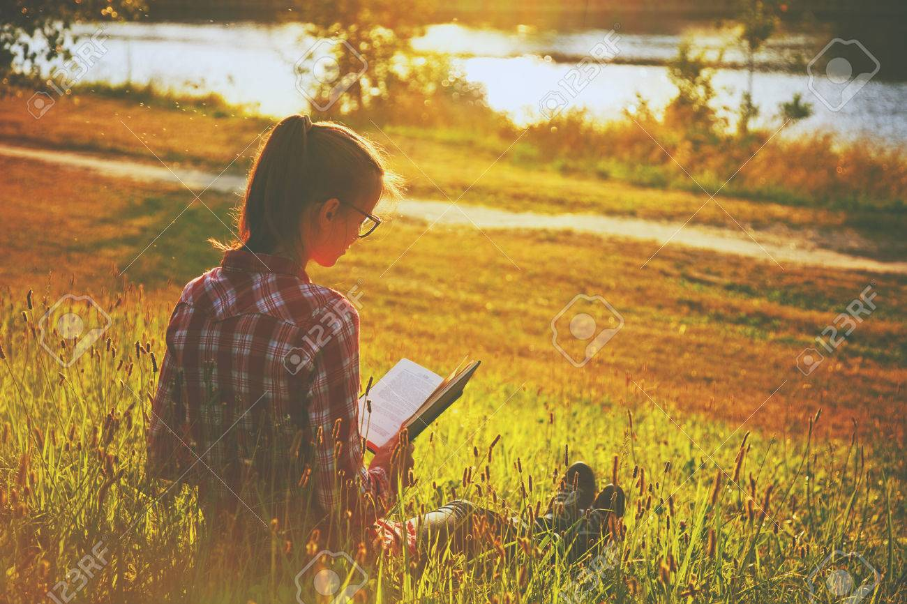 Girl reading book on summer shore of river Stock Photo - 46674955