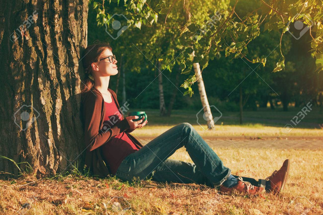 Smiling girl with cup of tea or coffee enjoying near park tree in morning sunlight Stock Photo - 46675058