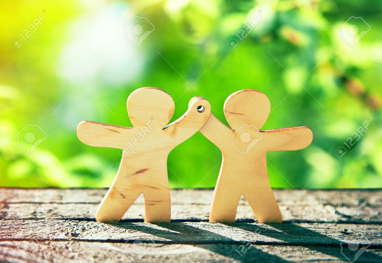 Wooden little men holding hands on natural green background. Symbol of friendship, ecology and teamwork Stock Photo - 46649873