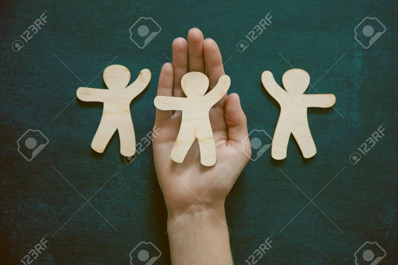 Hands holding little wooden men on blackboard background. Symbol of friendship, love or teamwork concept Stock Photo - 46649742