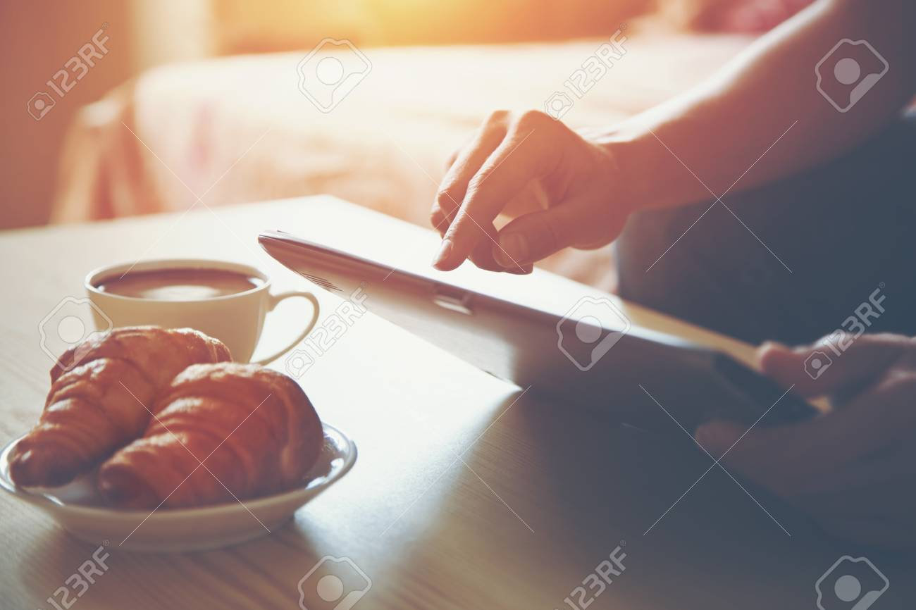Hands holding digital tablet pc with morning coffee and croissant. Stock Photo - 46649747