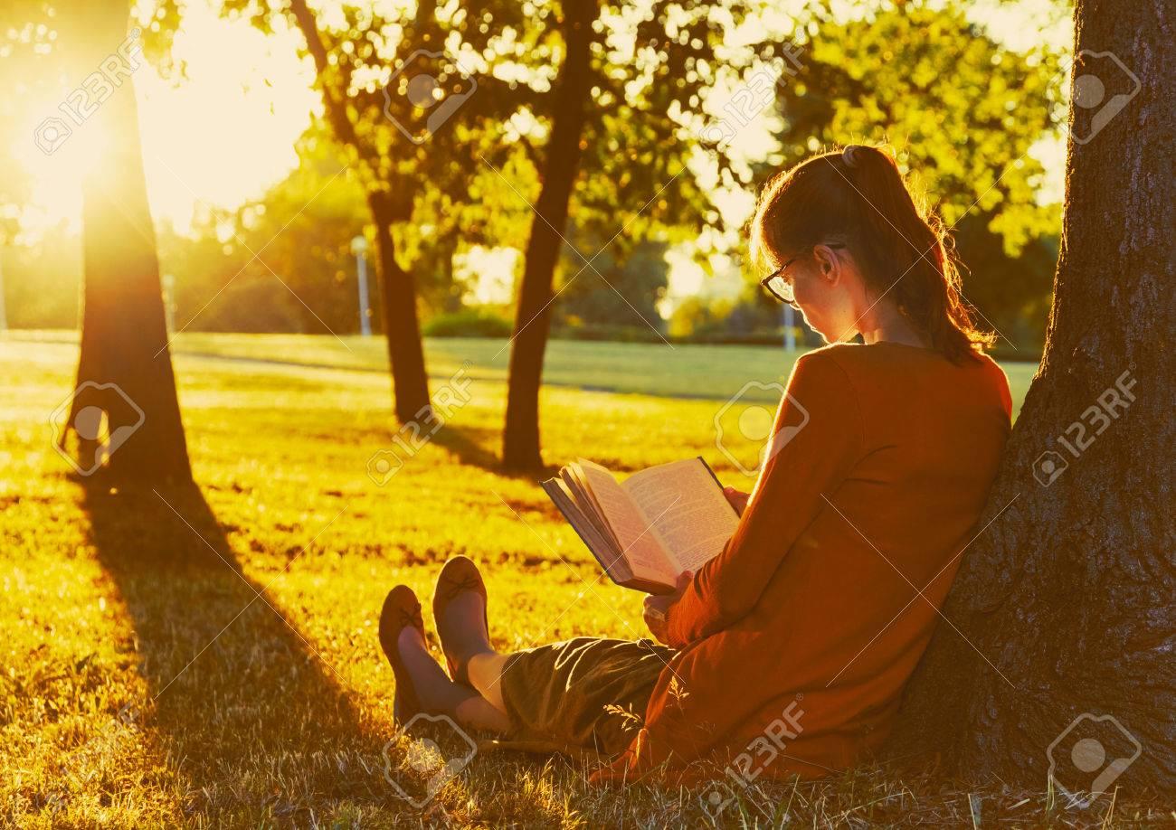 girl reading book at park in summer sunset light Stock Photo - 46675064