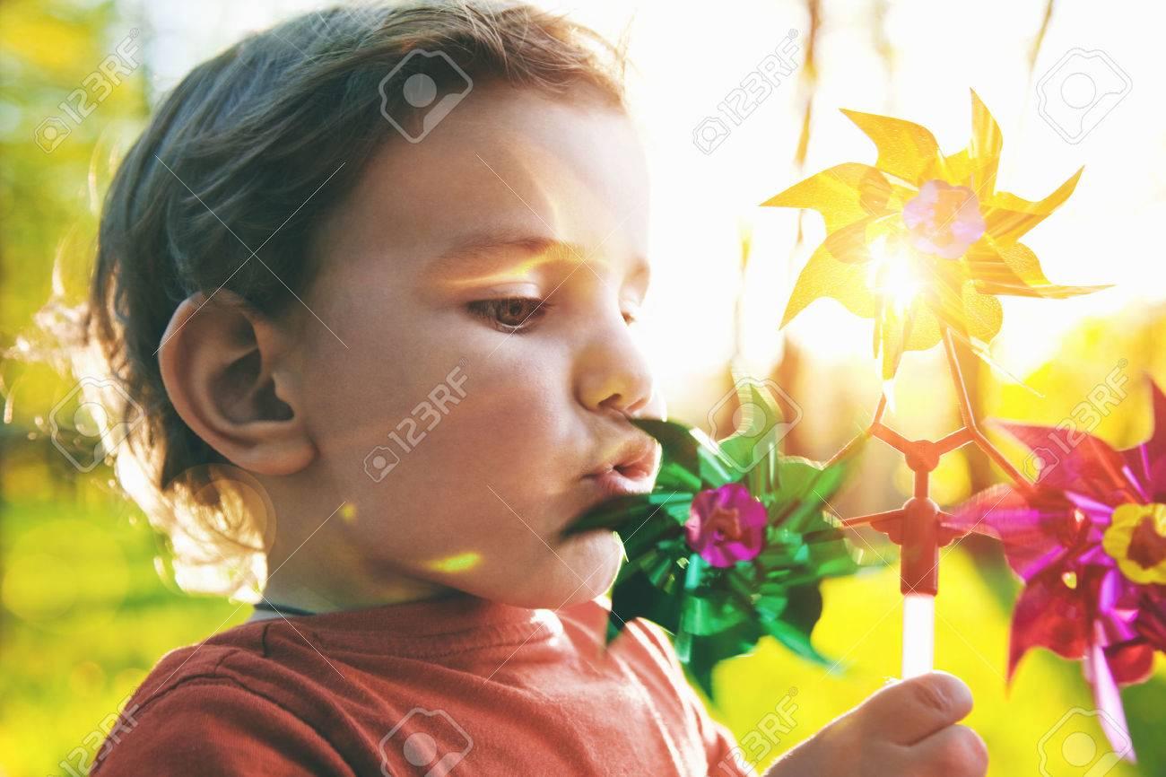 Portrait of a cute boy blowing wind wheel in sunshine Stock Photo - 46782827