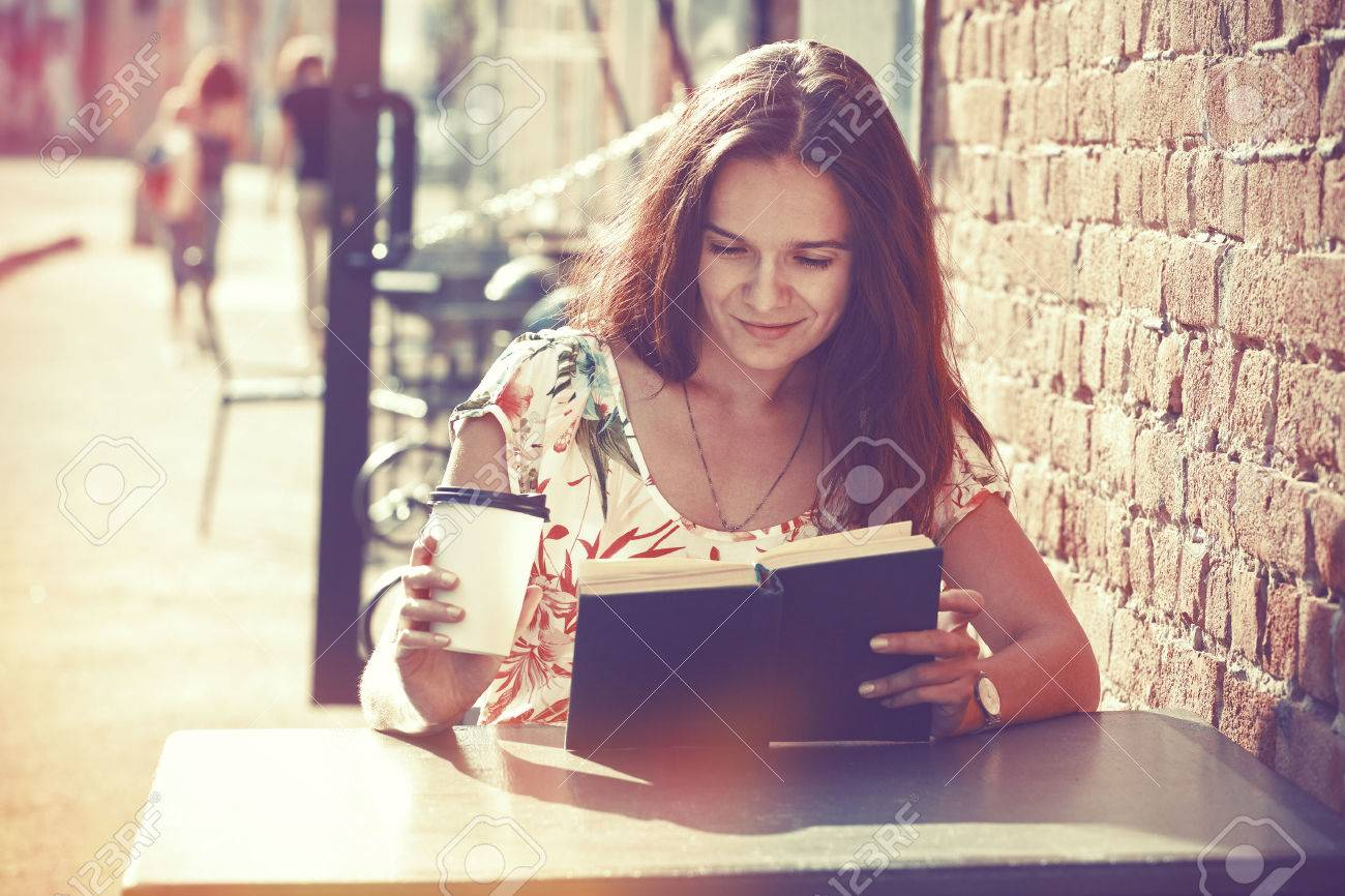 smiling girl sitting at summer terrace in street with morning coffee and reading book Stock Photo - 57077050