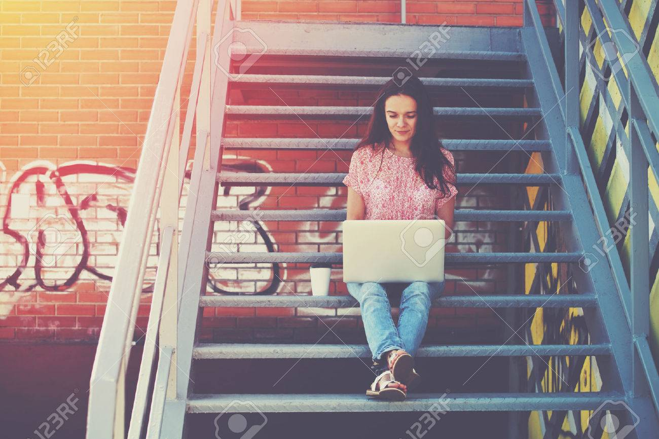 Pretty girl working with laptop sitting on stairs of stairway Stock Photo - 46675068