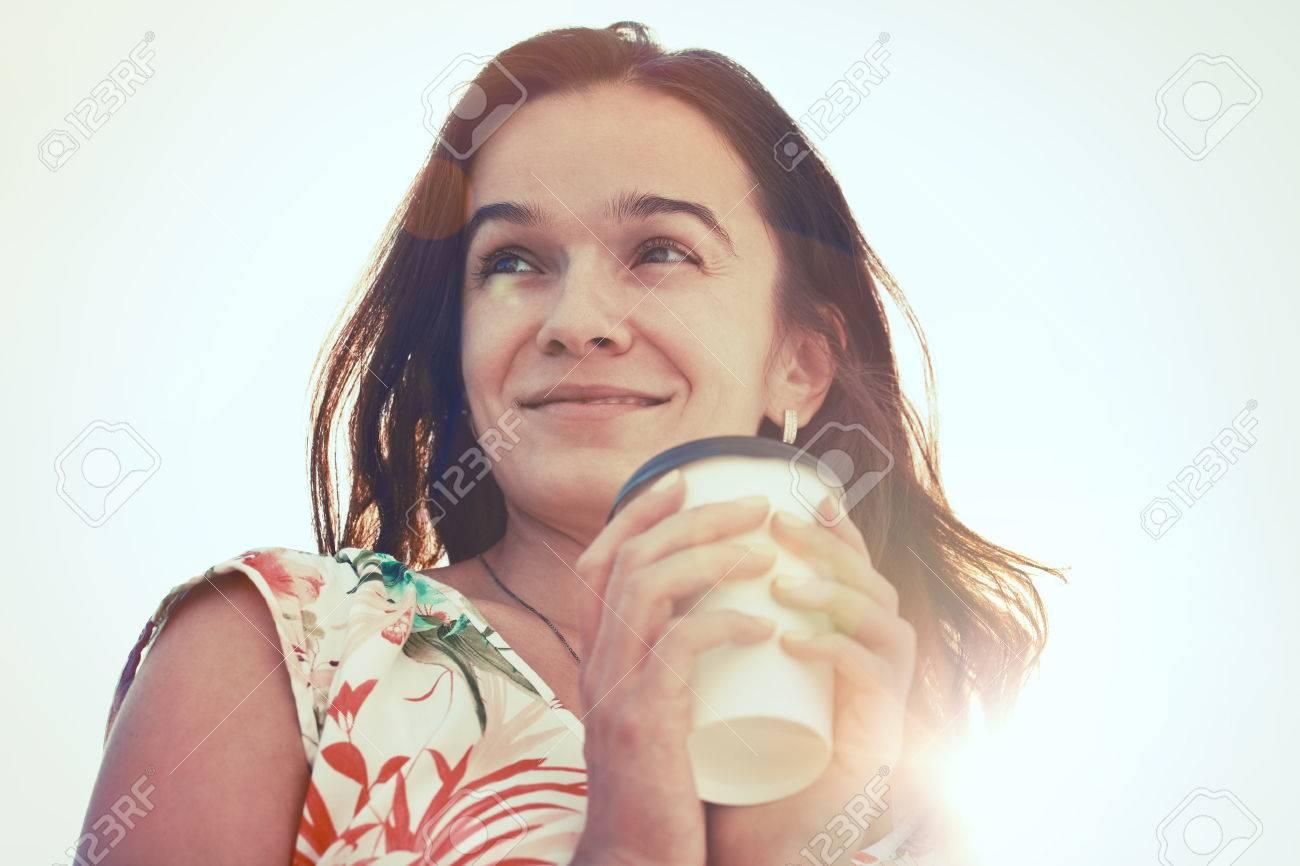 1b8f20e66f82 Archivio Fotografico - Bella ragazza sorridente con il caffè del mattino  alla luce del sole