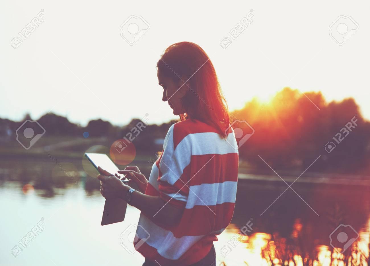 girl holding digital tablet pc at lake shore in sunrise light Stock Photo - 46784256