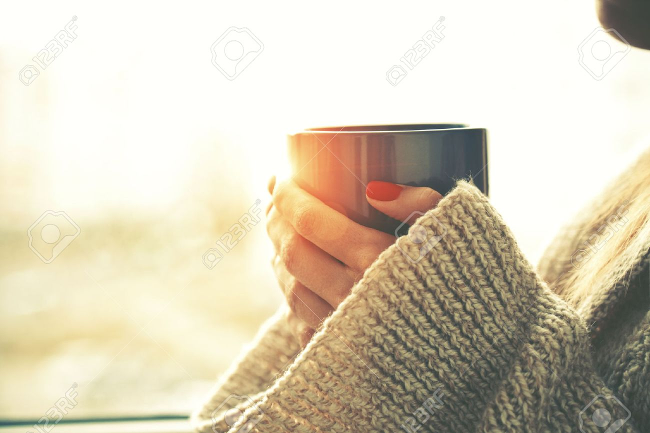 hands holding hot cup of coffee or tea in morning sunlight Stock Photo - 47461043
