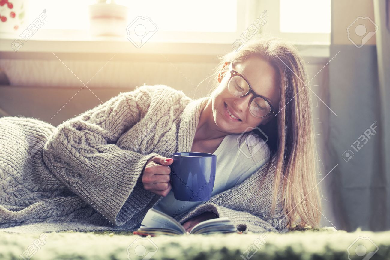 pretty girl reading book with morning coffee lying in bed Stock Photo - 47498989