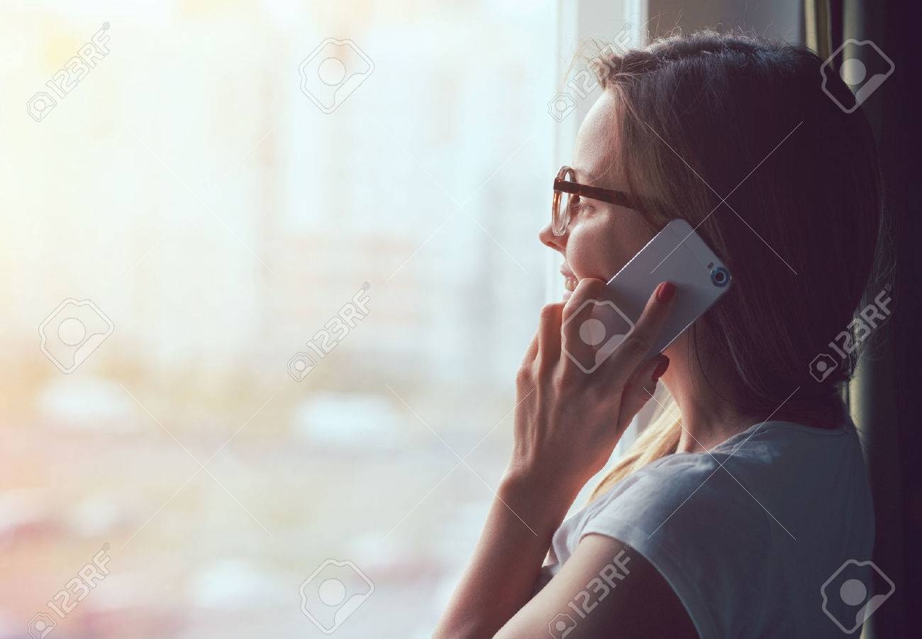 pretty woman talking on phone near window at home in morning sunlight Stock Photo - 47462644