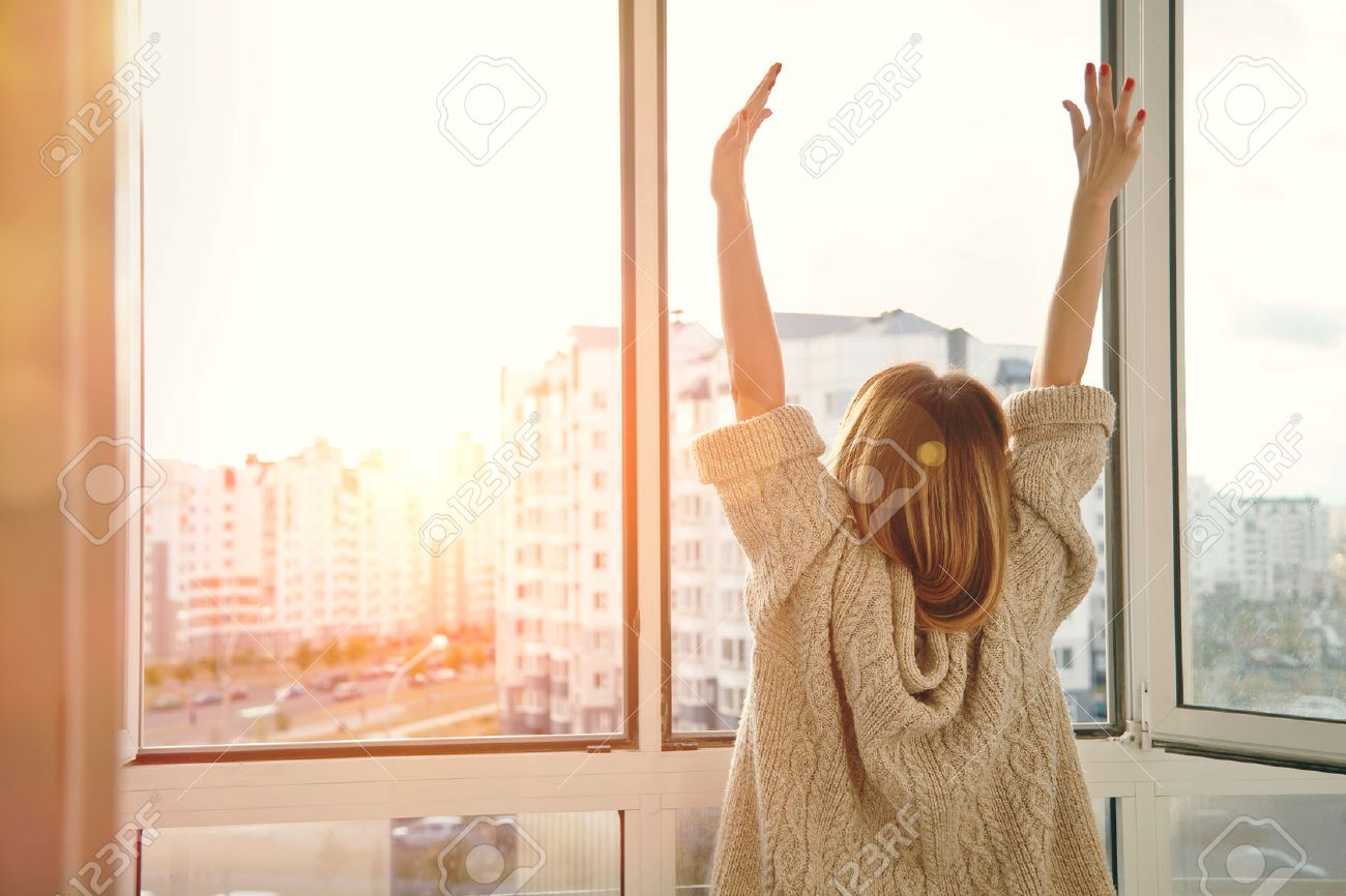 Woman near window raising hands facing the sunrise at morning Stock Photo - 47462646