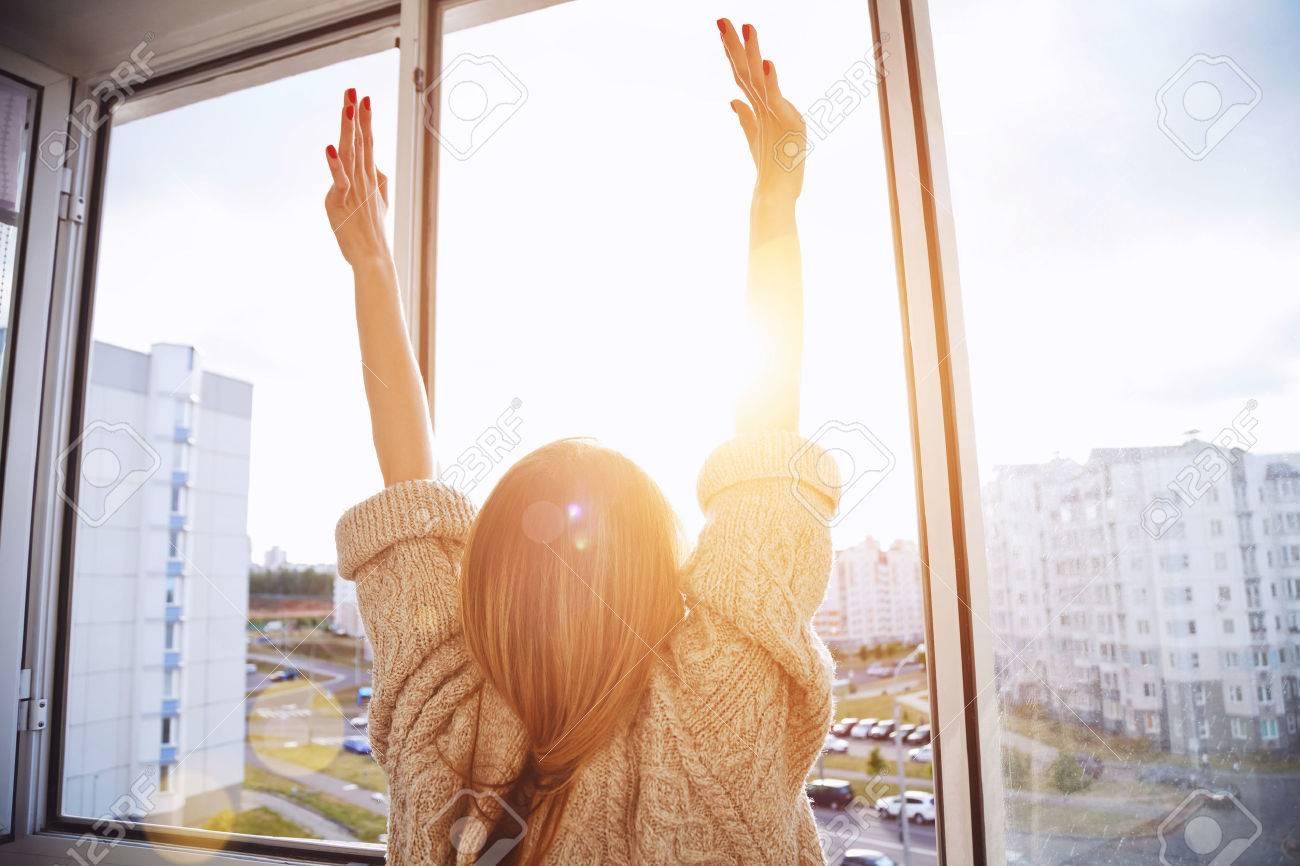 Woman near window raising hands facing the sunrise at morning Stock Photo - 47462811