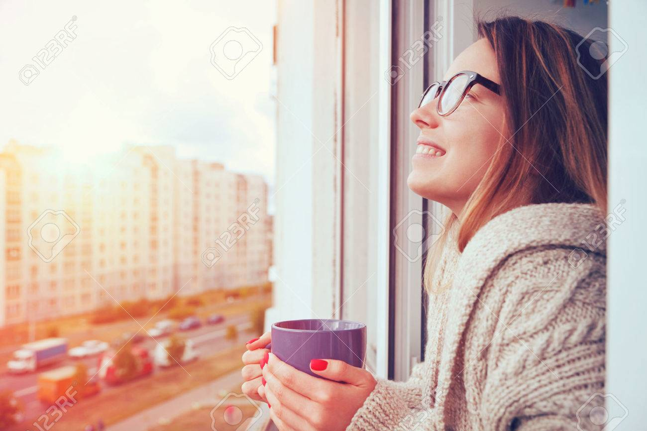cheerful girl drinking coffee in morning sunlight in open window Stock Photo - 46806335
